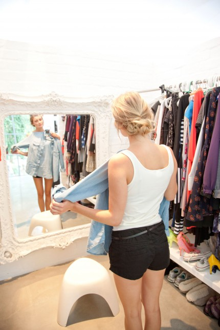 Woman in Closet Looking in Mirror Holding Shirt