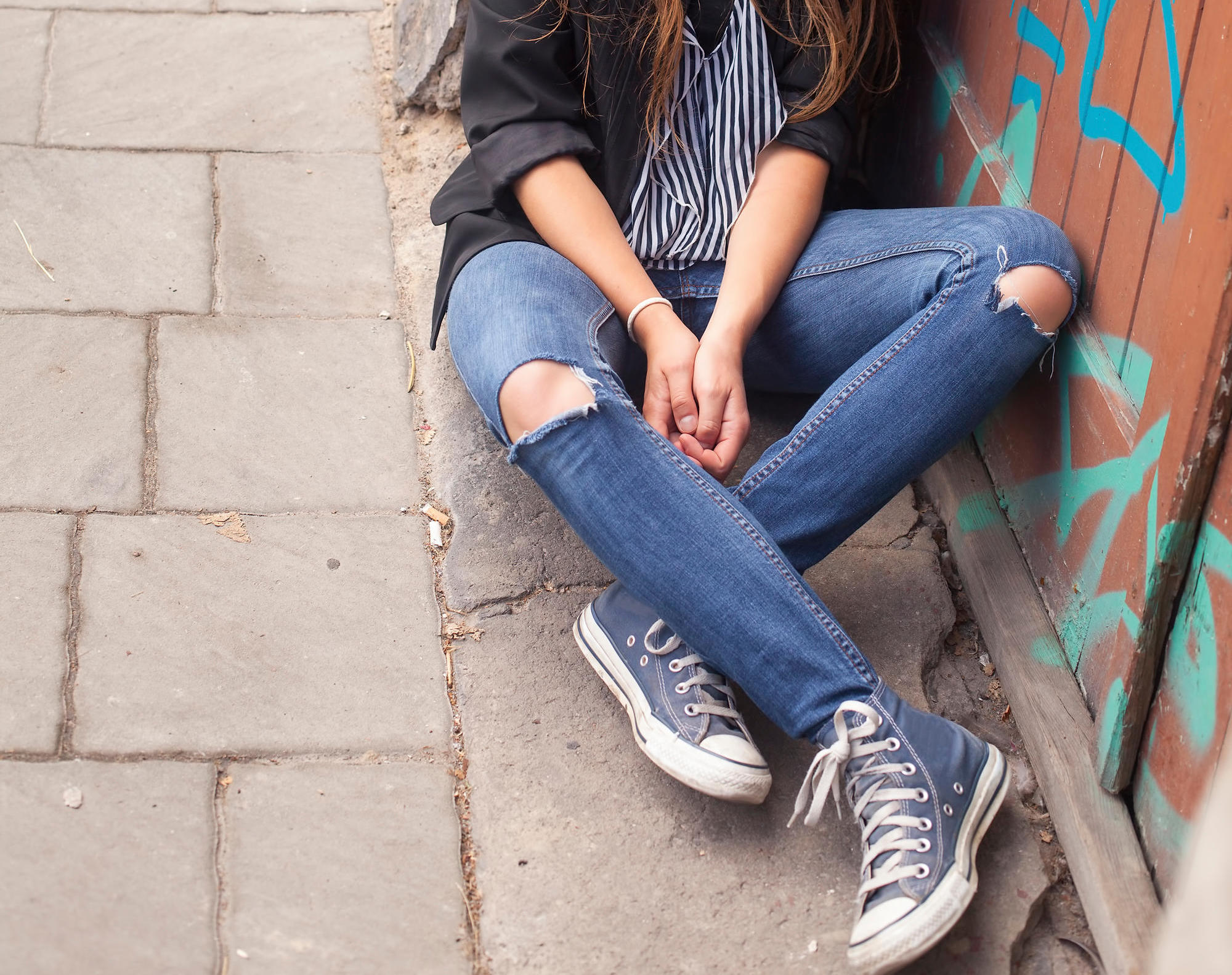 Young hipster girl sitting on the street.