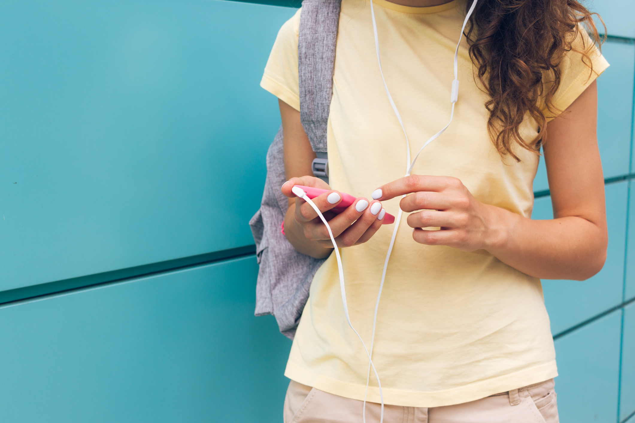 Close-up of female hands with white manicure holding pink mobile phone and headphones outdoors near a blue wall