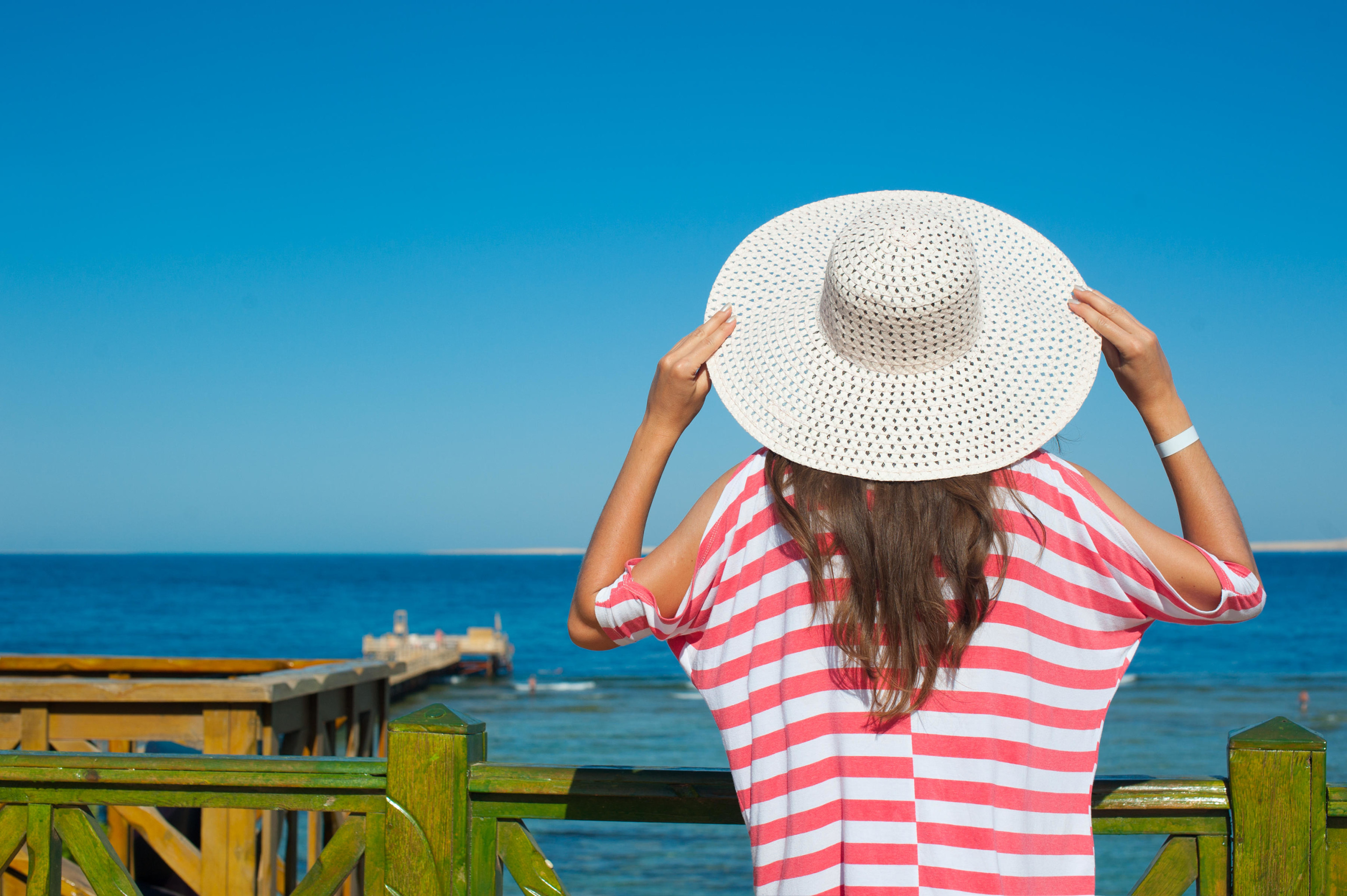 woman in a big hat looking at the sea.