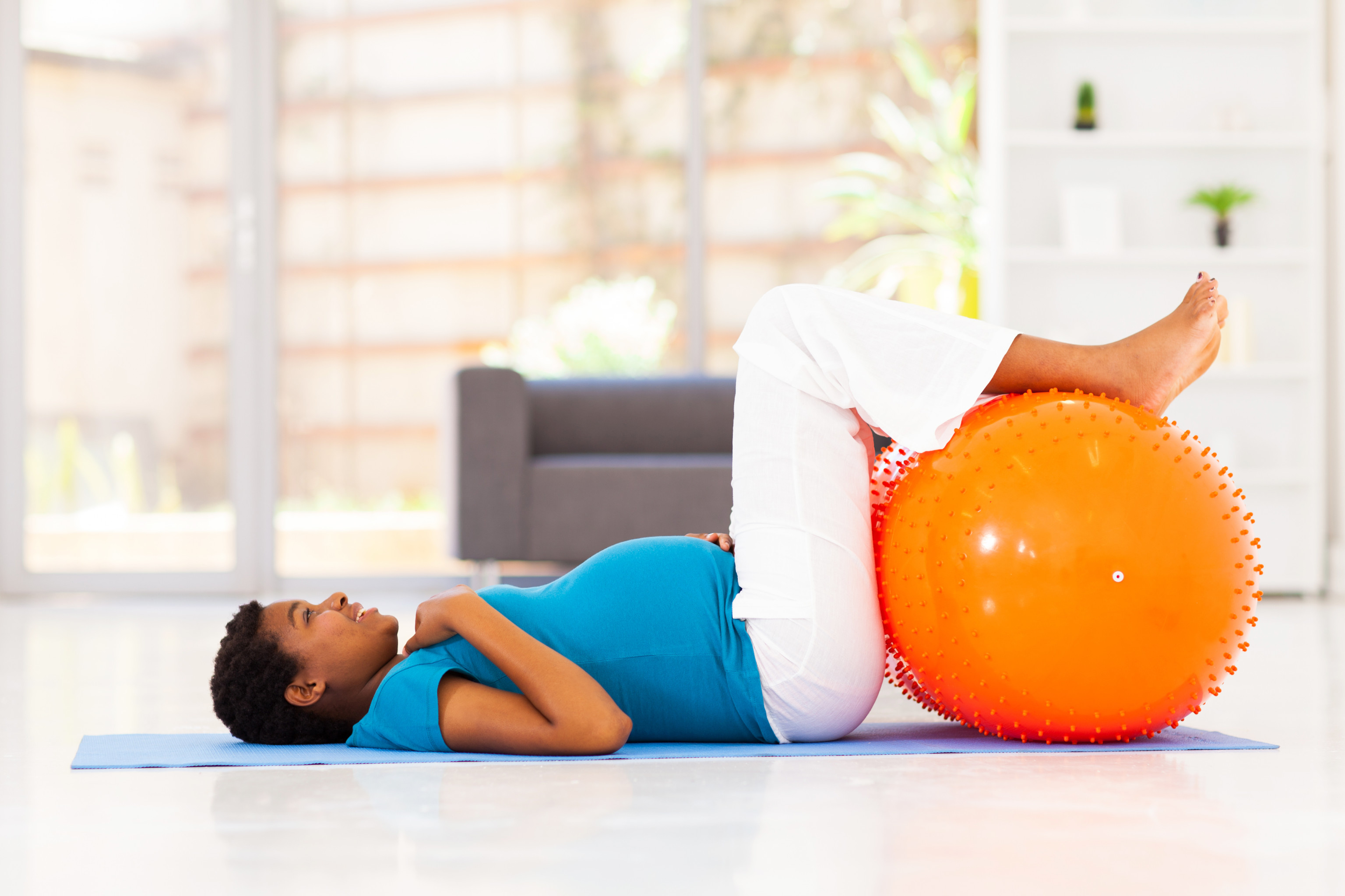 pregnant african woman workout on exercise mat